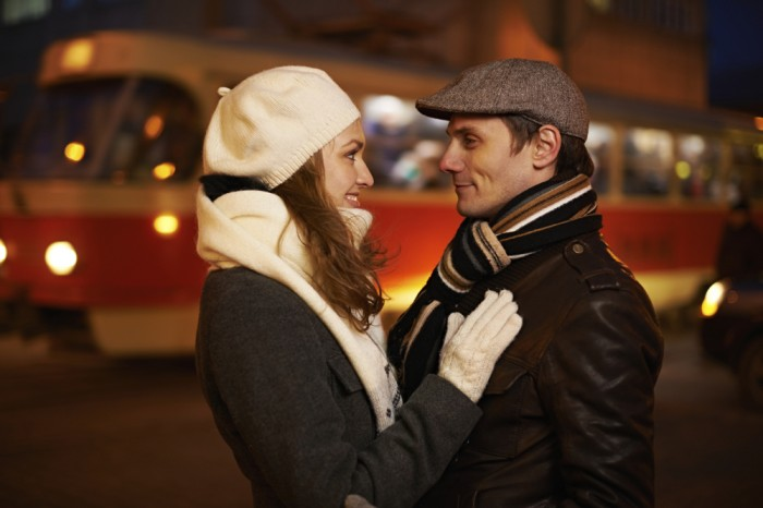 Adorable young couple standing face to face on railroad station