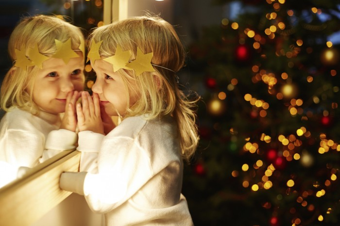 little girl standing near the mirror in Christmas eve