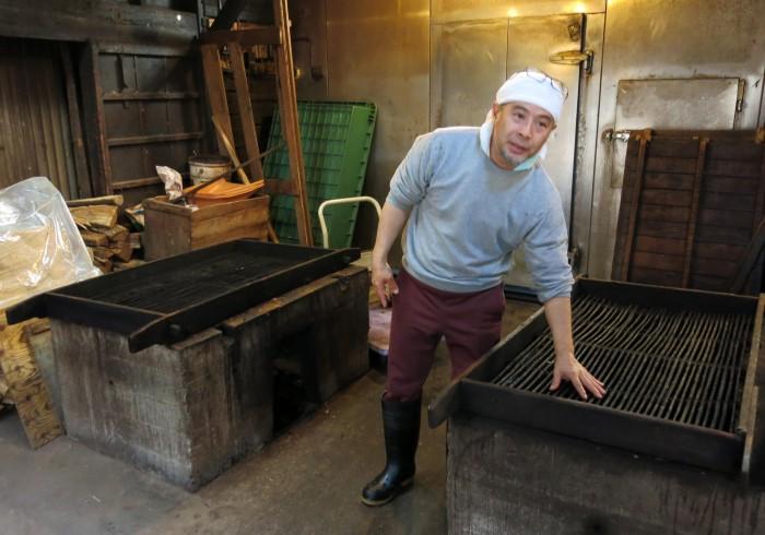 店主の芹沢里喜夫さんと焙乾炉。地元の薪を使用して行う。