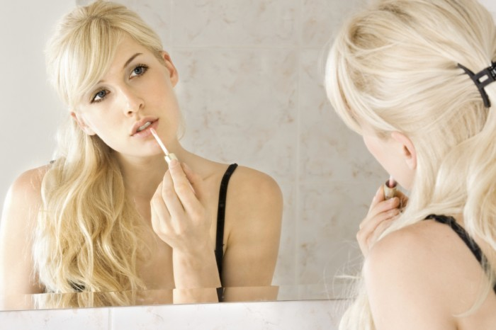 young woman applying lipstick in front of mirror