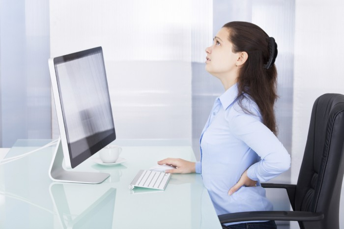 Portrait Of Young Businesswoman Suffering From Back Pain