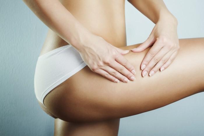 Youn woman squeezing leg to show no cellulite
