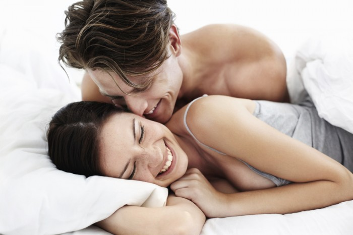 Cute young woman in bed with her loving partner