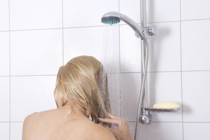 young woman washing long hair in shower