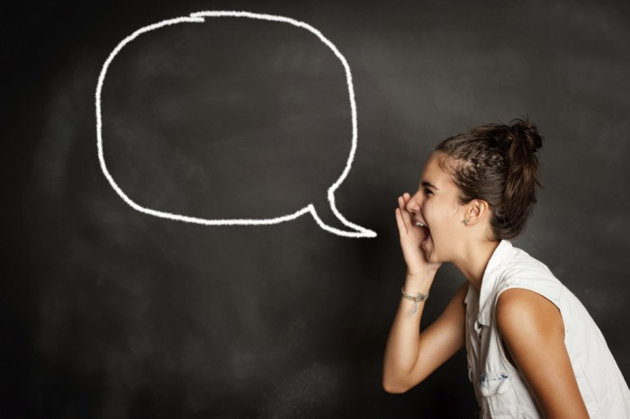 portrait of young girl screaming in front of chalkboard with speech bubble
