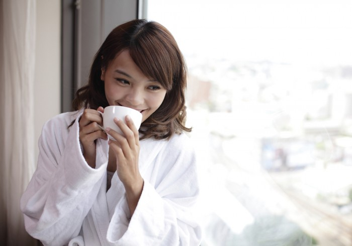 Young attractive woman , holding a cup of coffee, smiling.