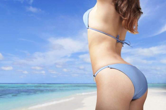 beautiful young woman in sexy bikini at the beach, back view