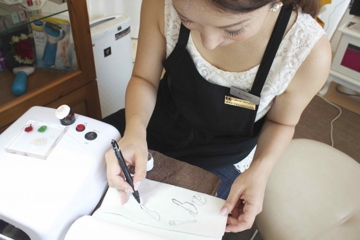 ナプキンの上で絵のデザインの下書きをする津野さん
