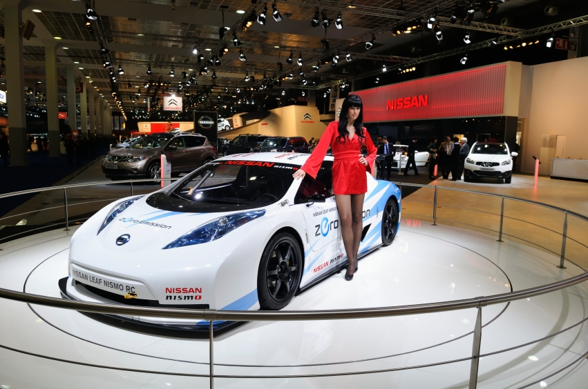 Nissan Leaf Nismo RC full electric race car with a model standing next to it on display during the 2012 Brussels motor show.