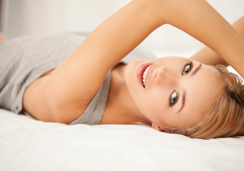 Chill time. Smiling young blond hair woman in singlet lying on bed and looking at camera
