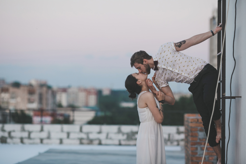 beautiful couple together on the roof of a tall building