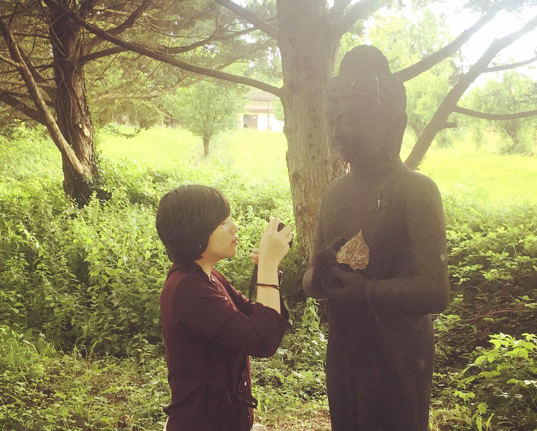 ハート型の枯葉を仏陀像の胸にのせて写真を撮るアン。彼女のお気に入りの場所で久石譲さん作曲のジブリ音楽を聞きながら、ケーキを一緒に食べました。
