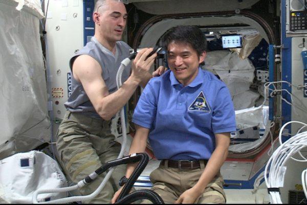 アナトーリ・イヴァニシン宇宙飛行士に散髪をしてもらう大西卓哉宇宙飛行士「デスティニー」(米国実験棟)