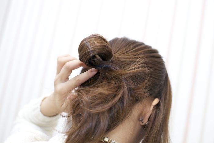 3:ポニーテールをつくる手前で毛束をゴムに通し切らずに留め、お団子を作る