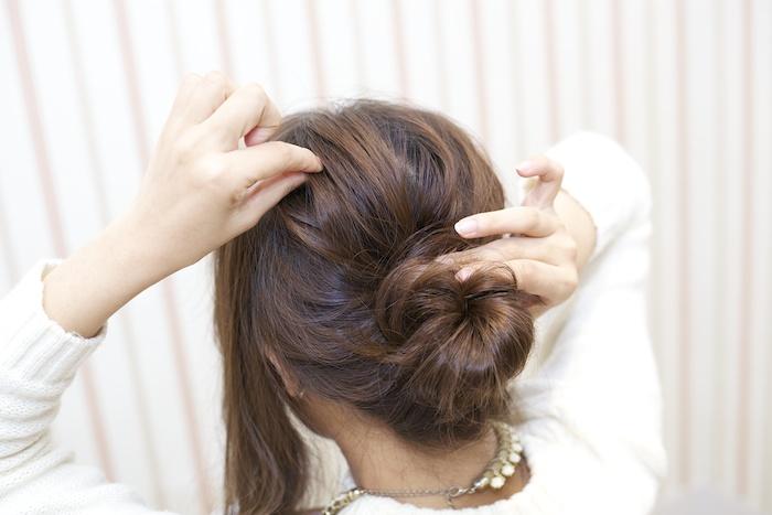 6:結び目をおさえながら毛束を引き出し立体感を出す。お団子の毛束も引き出し、丸みを整える。