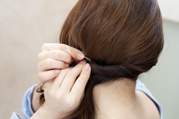 2:右側の髪の毛をすべて左側のえり足をめがけてねじり、一度ピンで固定します。