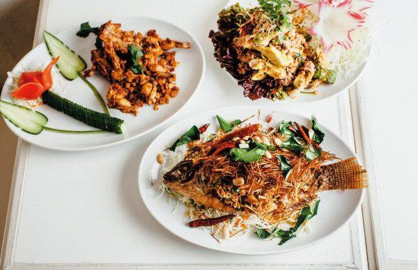 左から時計回りに、カエルのニンニク風味揚げ¥1,000、タイ風アボカドのサラダ¥1,280、プラー・サムンプライ(揚げ魚の香草添え)¥1,500。メニューはアラカルトのみ。一皿1000円台で2~3人でシェアできるボリューム。「好きなものを好きなように食べてほしい」というタムさんの想いを込めたリーズナブルな値段だ。
