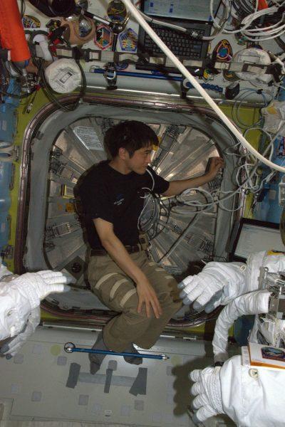 船外活動に向けて、船外活動ユニット(EMU)の着用を支援する大西卓哉宇宙飛行士