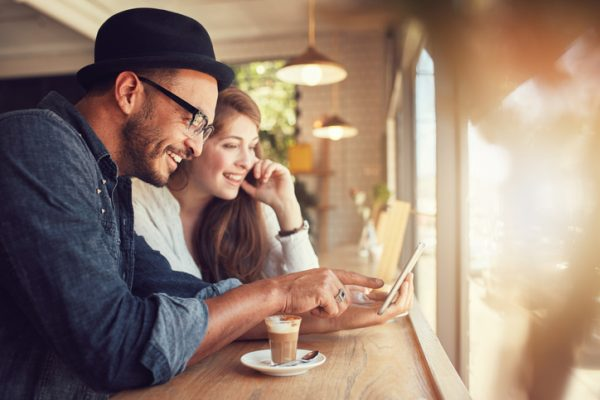 Couple using a digital tablet at coffee shop