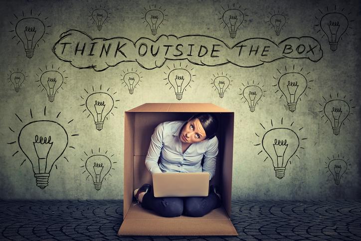 Think outside box. Woman sitting inside box