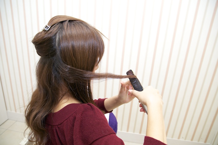 2:高めの位置でひとつに束ね、毛先をゴムに通し切らずに手前で止める。