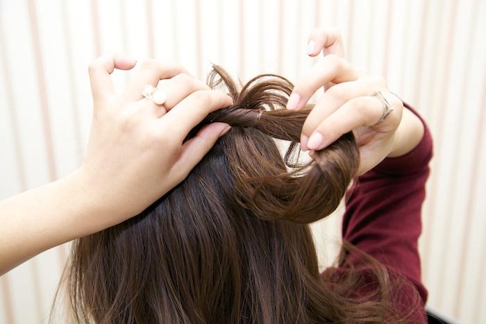 6:ピンを抑えながら、ロープ状の網目から髪の毛束を少しずつ引き出し、立体感を出す。余った毛先はそのまま下に流してなじませる。