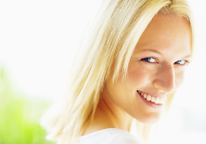 Closeup of a smiling pretty blond female looking at you