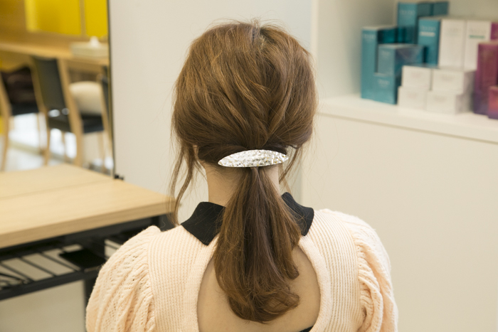8:結び目を抑えながら、毛束を少しずつ引き出してルーズ感を加える。