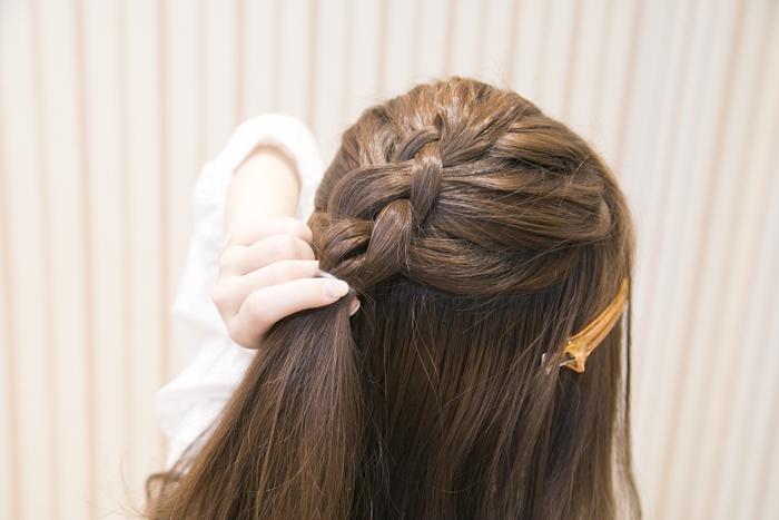 4:後ろの髪をきつめに編み込みする。3回ほど編み込んだら、1回三つ編みにする。