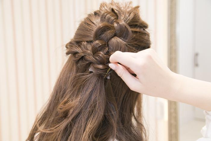 9:ねじった部分の毛先を結んでから、後ろの編み込み部分の髪と合わせ、ピンで止め、お好みのヘアゴムをつける。