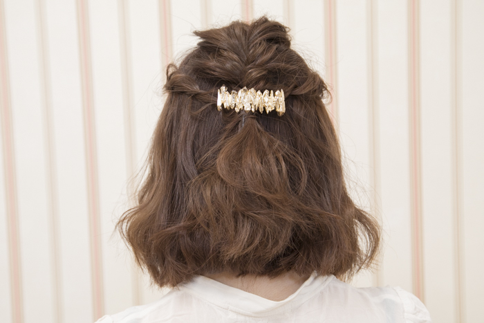 6:ピンを抑えながら、ロープ状の網目から髪の毛束を少しずつ引き出し、立体感を出す。余った髪の毛先はそのまま下に流してなじませる。