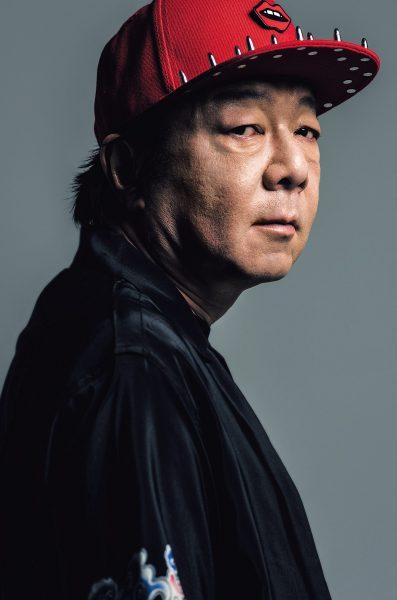 赤いキャップをかぶったこちらを振り返る古田新太の画像