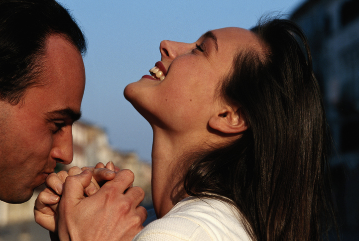 Young man kissing woman's hand, outdoors, smiling
