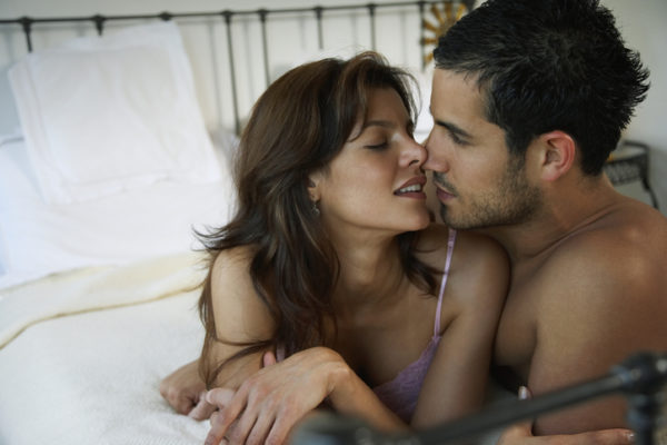 Hispanic couple kissing on bed