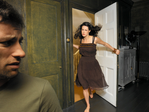 Woman in doorway scowling at man