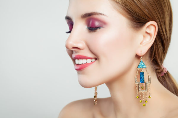 Pretty woman with makeup and gold earrings