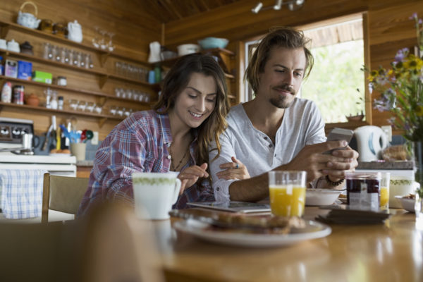 Young couple enjoying breakfast at cabin kitchen table