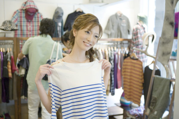 Young woman looking at cloth in clothing store