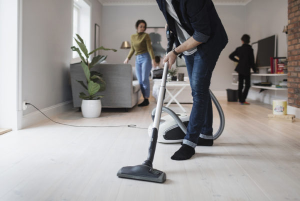 Low section of man vacuuming floor with woman and son in living room