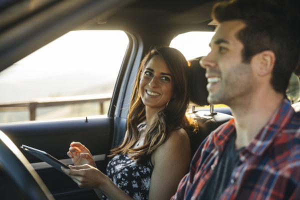 Happy couple in car using tablet computer