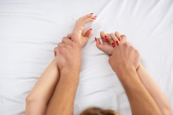 Hands of couple in bed.