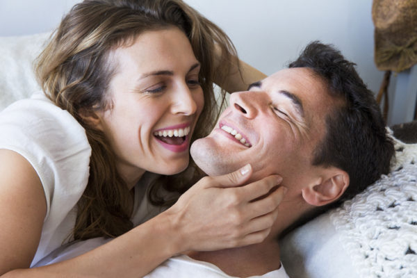 Couple lying together flirting and laughing