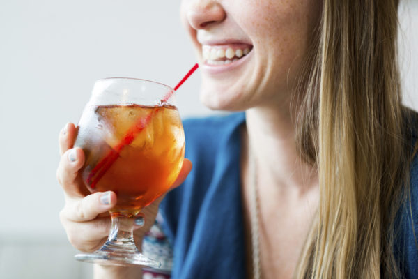 Midsection of smiling woman enjoying ice tea in cafe