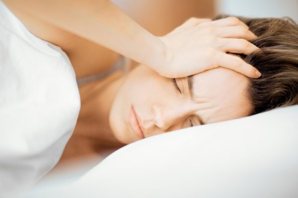 Close-Up Of Young Woman With Headache Lying On Bed