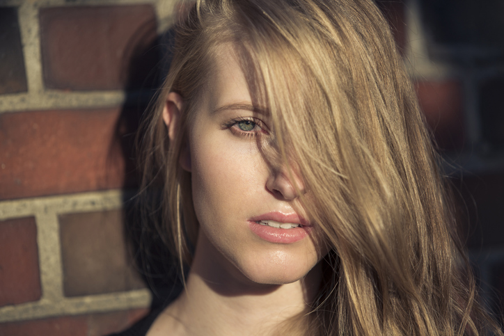 Portrait of blond young woman in front of brick wall