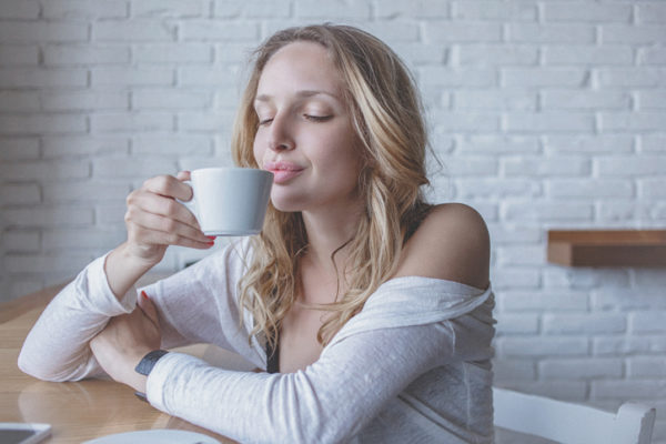 Young pensive woman at cafe enjoying fresh cup of coffee