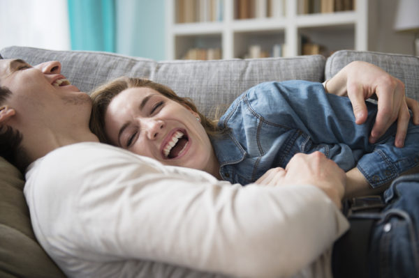 Couple laughing together on couch