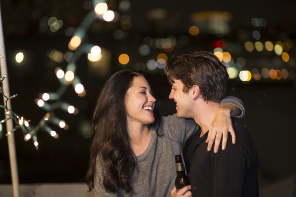 Young couple having fun at rooftop party