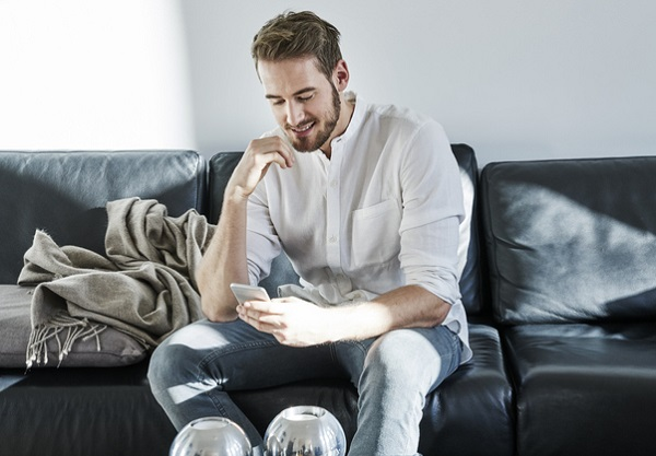 Smiling man sitting on couch looking at cell phone