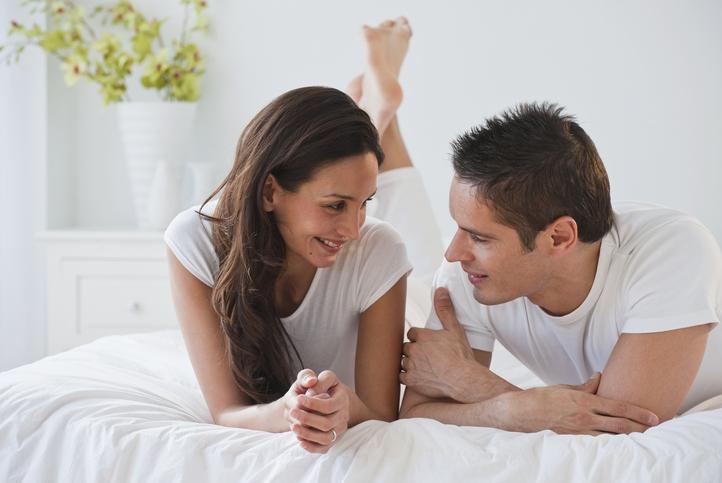 Hispanic couple laying on bed